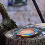 Holzschale bunt bemalt auf Holzstamm
