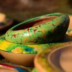 Holzschalen grün und gelb bemalt mit Tellern im Sonnenschein