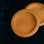 Zwei helle Holzteller mit verschiedenem Rand