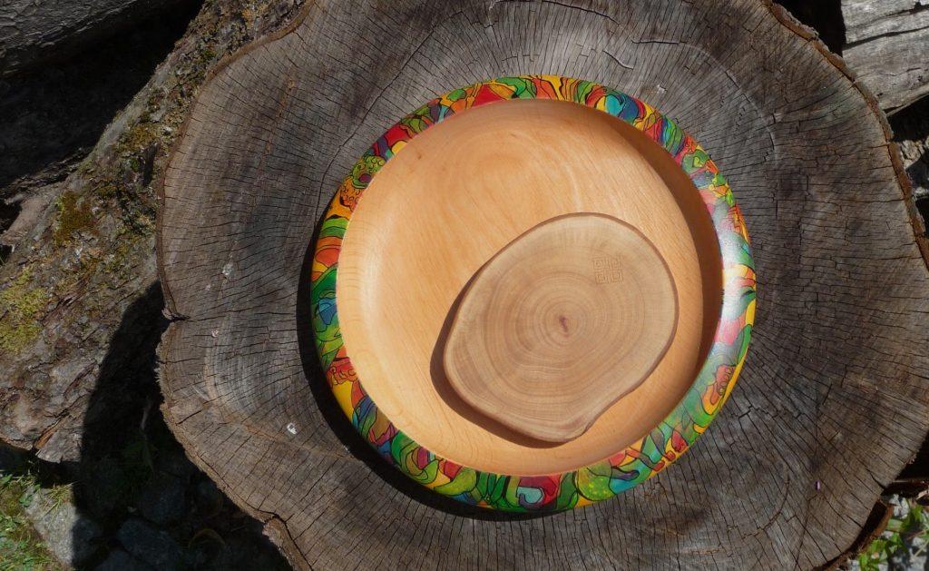 Titelbild für Unsere Arbeiten. Ein edler Untersetzer und ein bemalter Teller auf einem alten Baumstamm