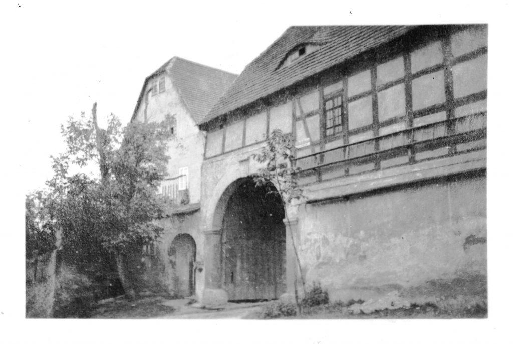 Alte Fotographie des Hoftores von ca 1932 mit jungem Walnussbaum und noch intakter vierter Seite des Gehöfts.