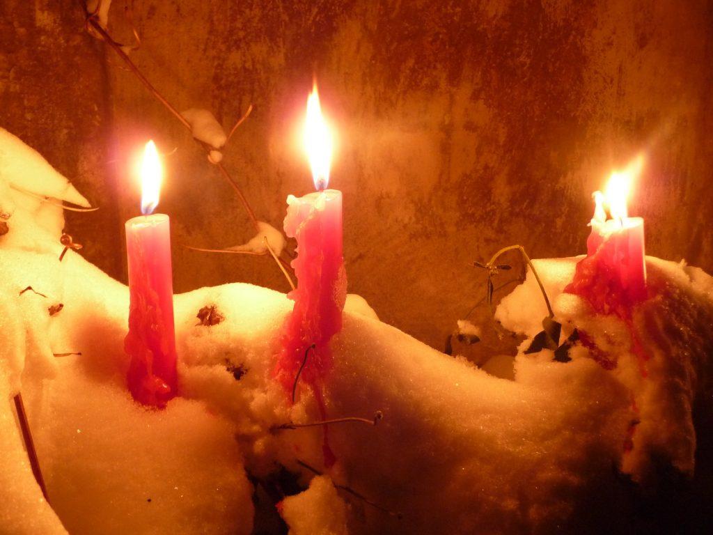 Drei rote Adventskerzen im Schnee